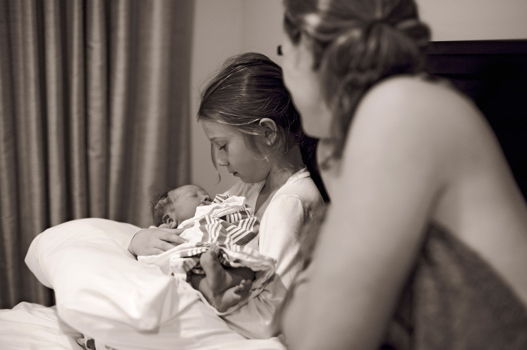 newborn birth sister holding baby happy family