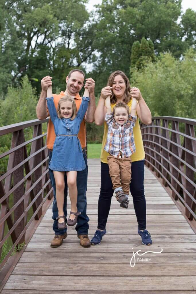 smiling happy family with children outdoors modern natural colorful on bridge