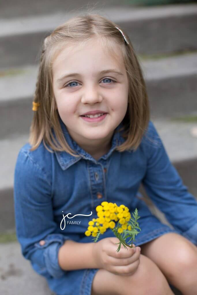 smiling child holding yellow flowers on steps