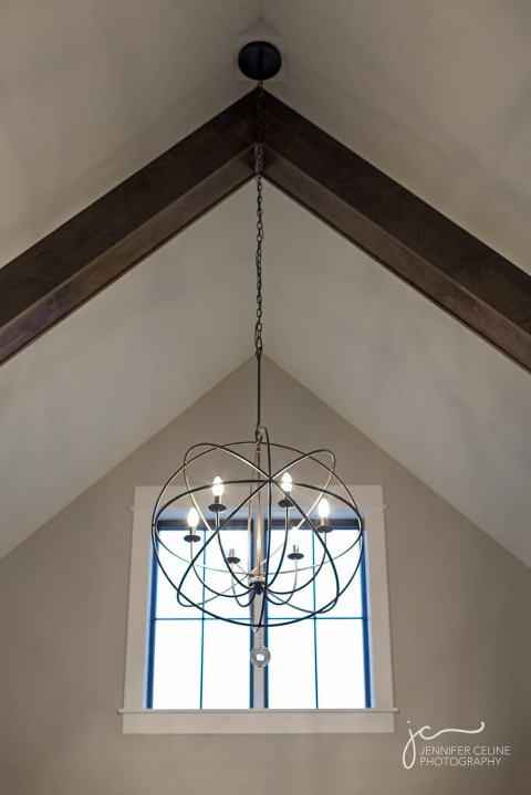 Swoon-worthy custom modern white farmhouse built by CBI Homes/Caritas Builders, entryway exposed wood beams