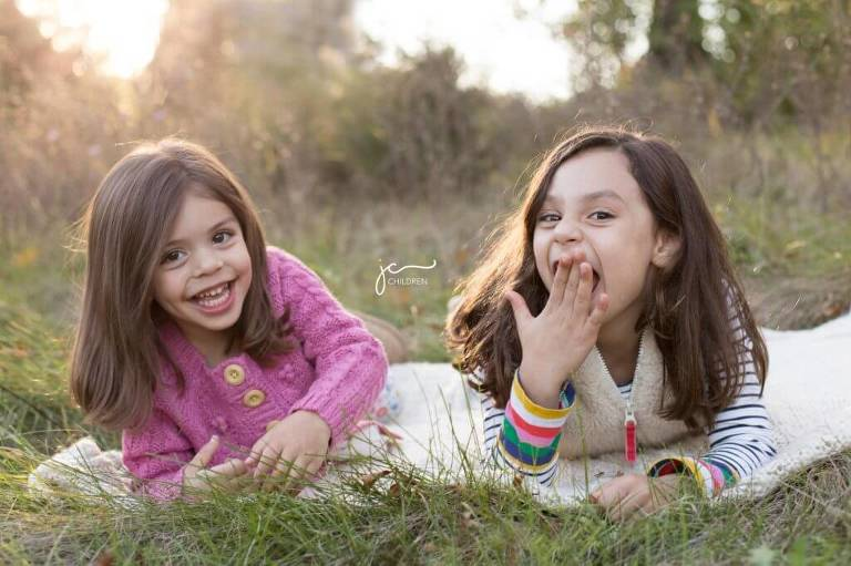 modern sweet giggly sisters in grassy field golden hour sunset