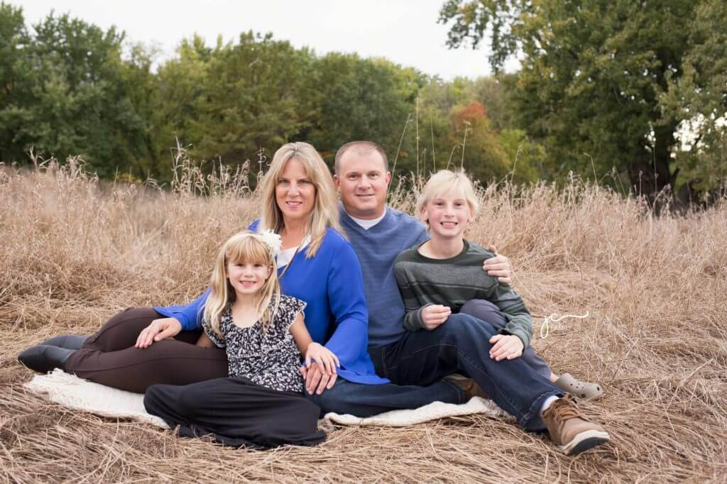 smiling happy family outdoors natural prairie grass