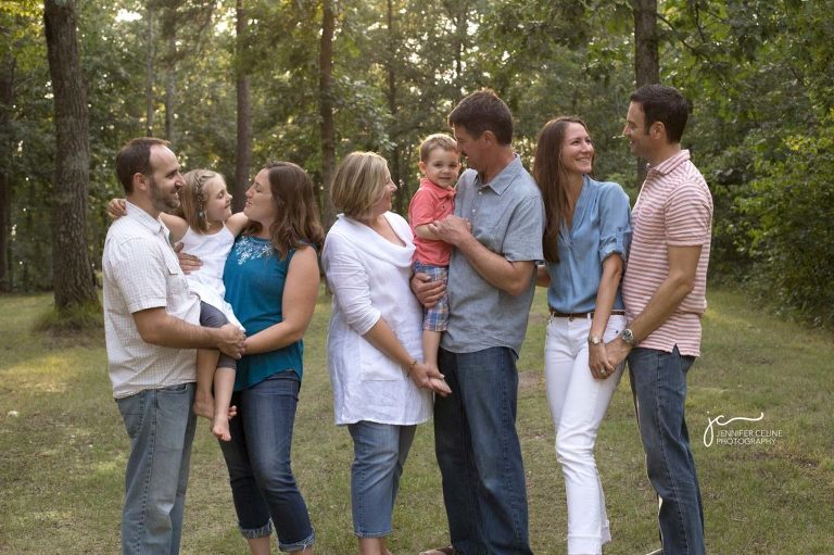 extended family, multi-generational family of 8, in woods of green trees foliage