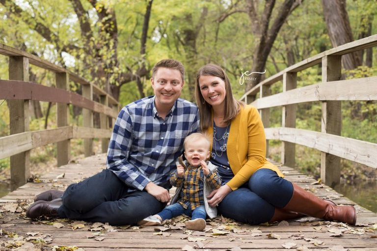 smiling happy family with child outdoors modern natural colorful on bridge