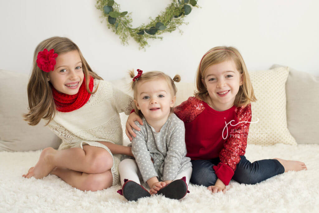 three young sisters dressed in holiday/Christmas outfit, sweet, modern, simple and festive with wreath