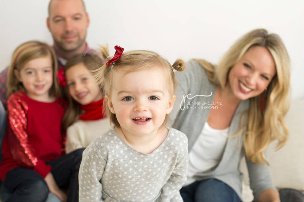 three young toddler walking toward camera with family blurred in background smiling in holiday/Christmas outfits, sweet, modern, simple and festive