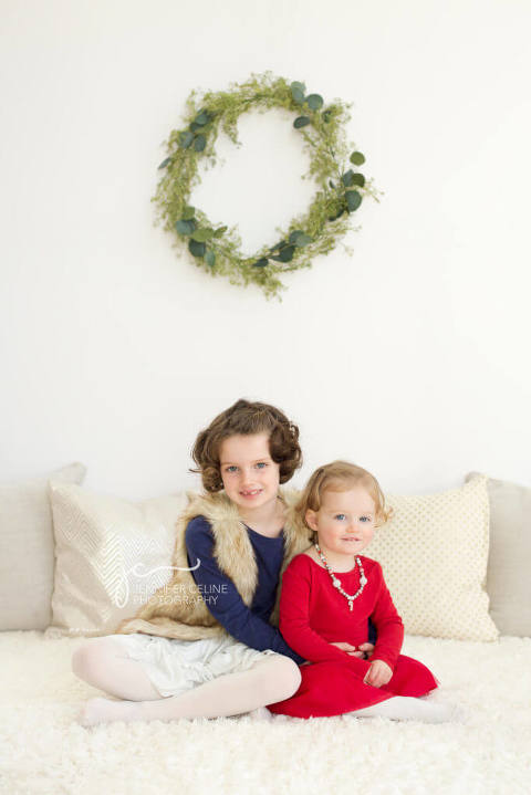 young girl siblings dressed in holiday/Christmas outfits, sweet, modern, simple and festive with wreath