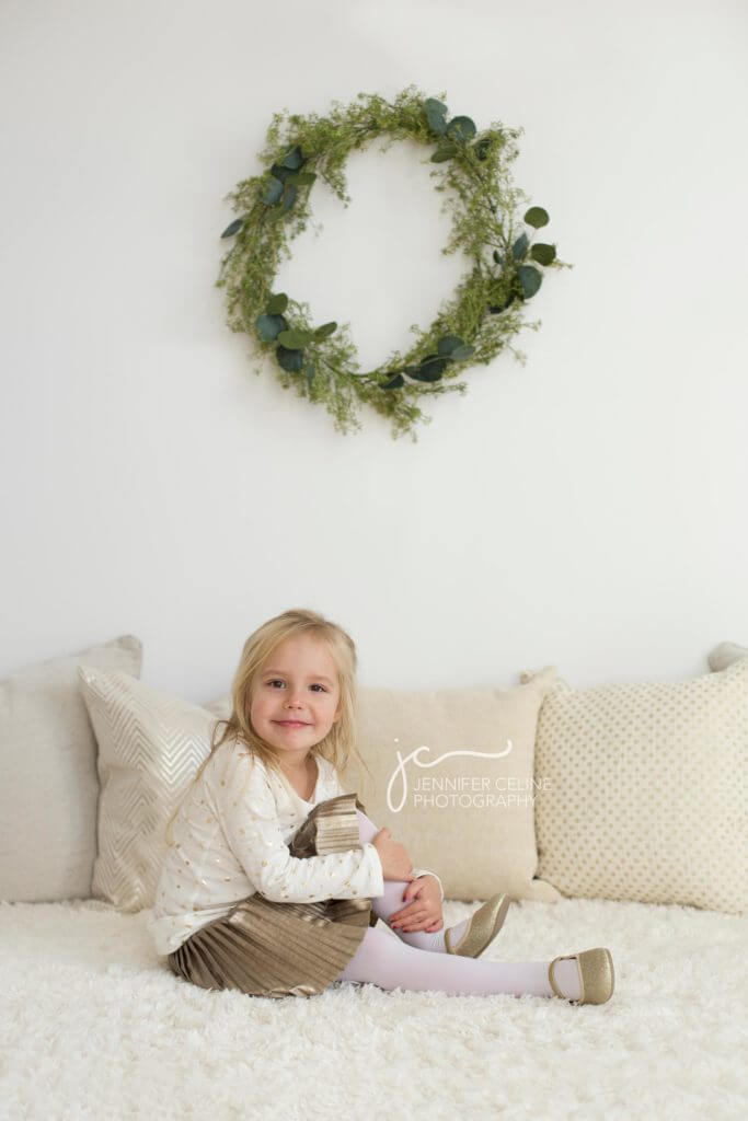 young girl dressed in holiday/Christmas outfit, sweet, modern, simple and festive with wreath
