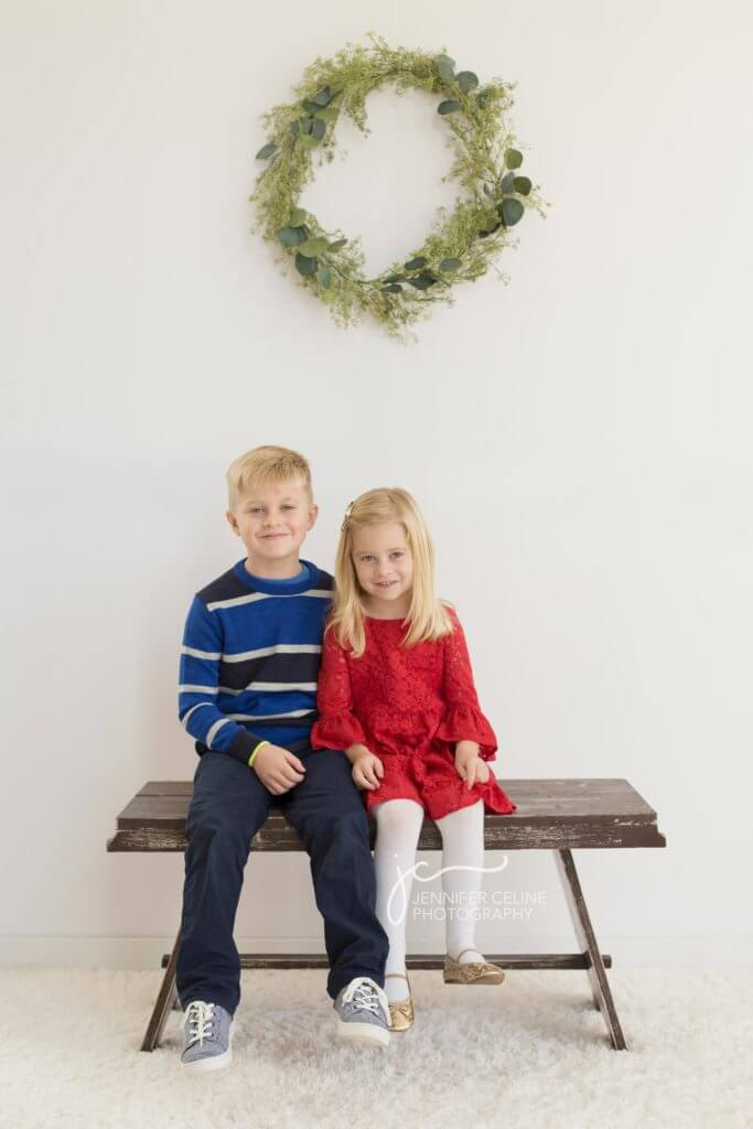young brother and sister dressed in holiday/Christmas outfits, sweet, modern, simple and festive with wreath