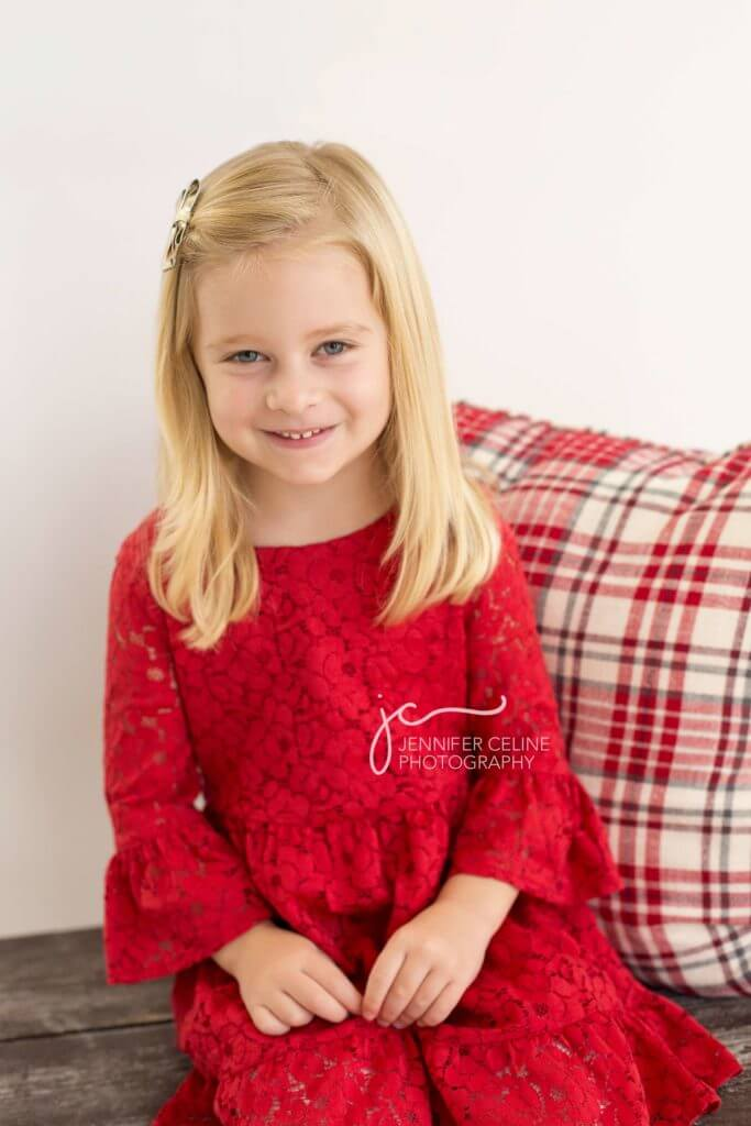 young girl dressed in holiday/Christmas outfit, sweet, modern, simple and festive with plaid pillow