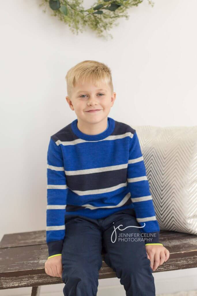 young boy dressed in holiday/Christmas outfit, sweet, modern, simple and festive with festive pillow