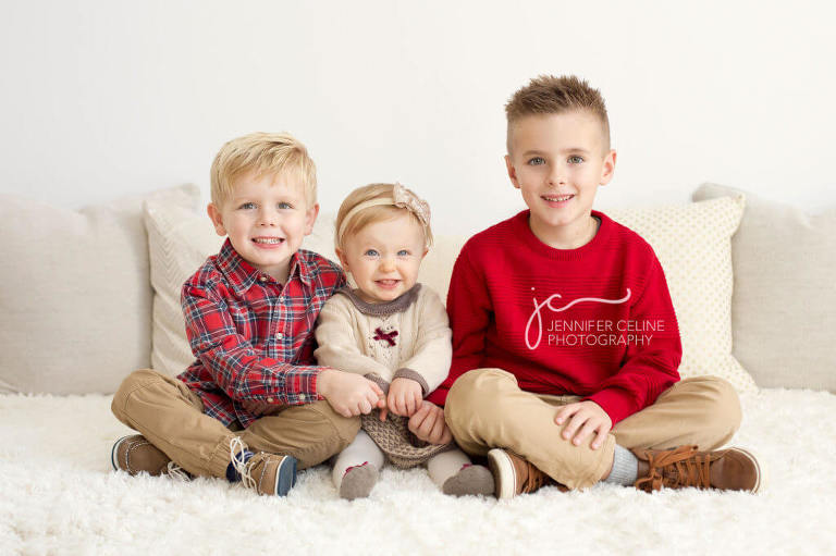 young siblings dressed in holiday/Christmas outfits, sweet, modern, simple and festive