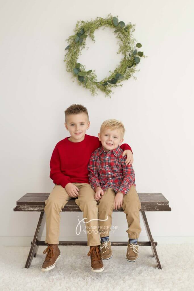 young brothers dressed in holiday/Christmas outfits, sweet, modern, simple and festive with wreath and rustic bench