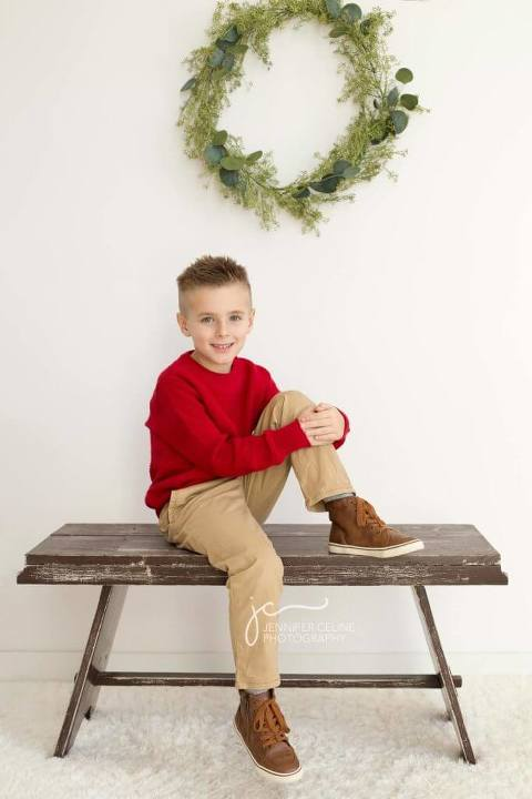 young boy dressed in holiday/Christmas outfits, sweet, modern, simple and festive with wreath and rustic bench