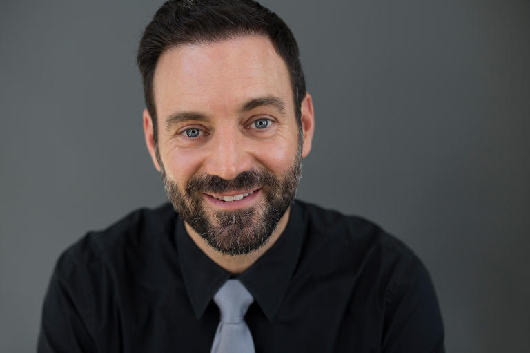 Business headshot of attractive, smiling, bearded caucasian man with blue eyes in black shirt with gray tie
