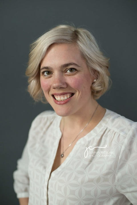 professional headshot of a smiling caucasian woman in white blouse against a gray backdrop
