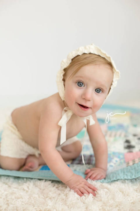 9 month old smiling baby girl with blue eyes in lace bonnet and bloomers on vintage quilt