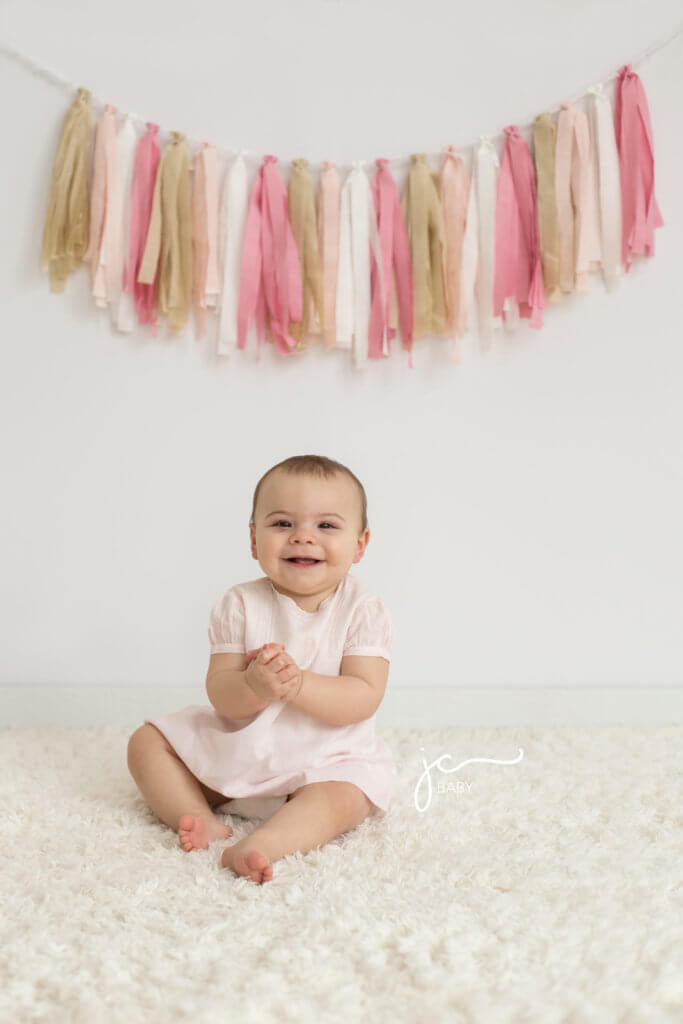 10 month old smiling, happy baby girl in vintage light pink dress with pink fabric garland