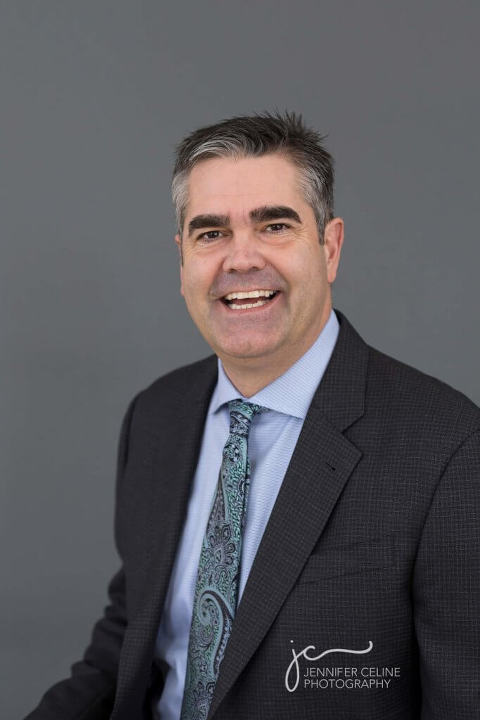 Professional headshot of business man in suit and tie