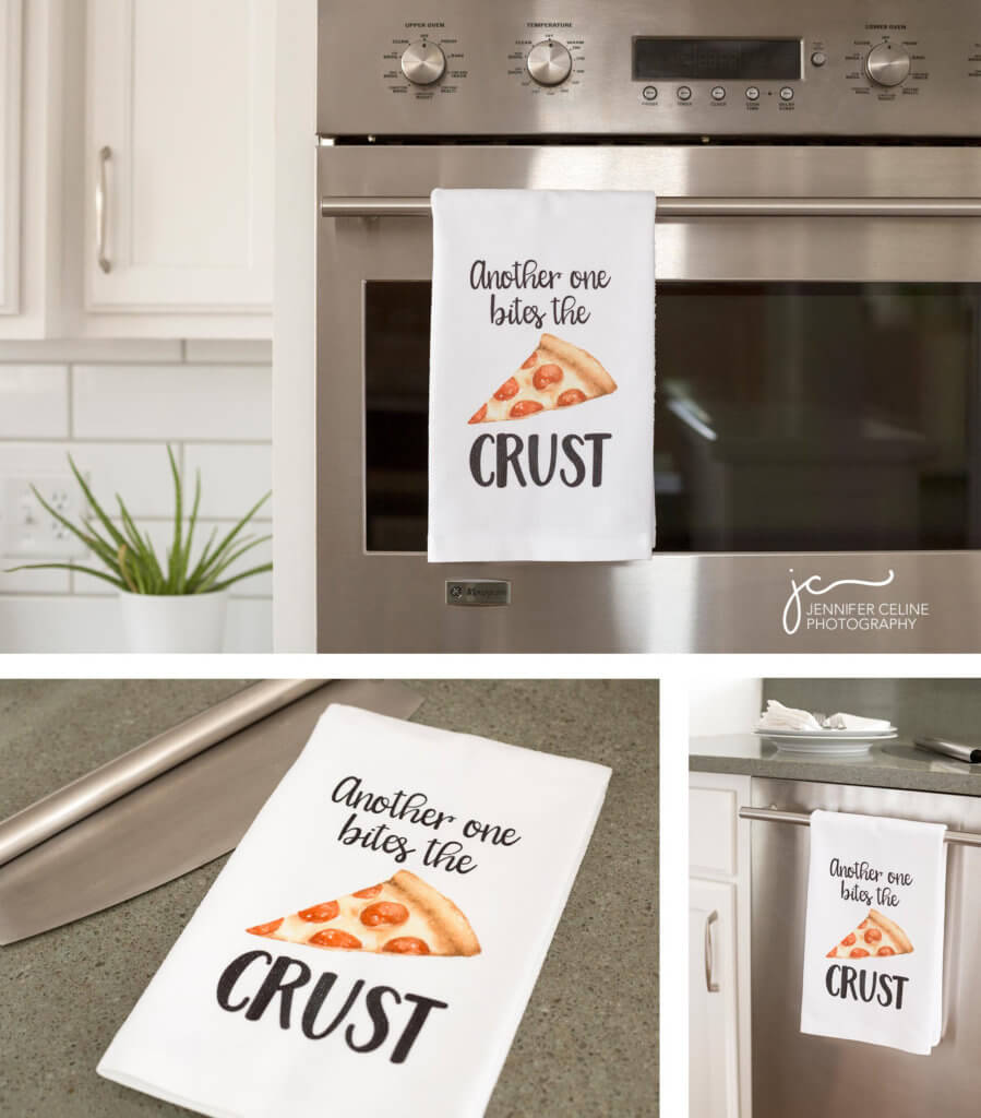 """Images of kitchen towels in a modern kitchen with a fun graphic that says """"another one bites the crust"""" printed on them."""