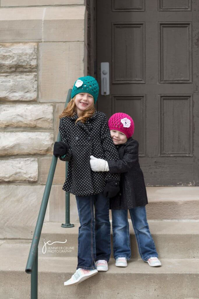 Young sisters in jackets and bright colored caps hugging while standing on steps in front of a brick building with weathered door