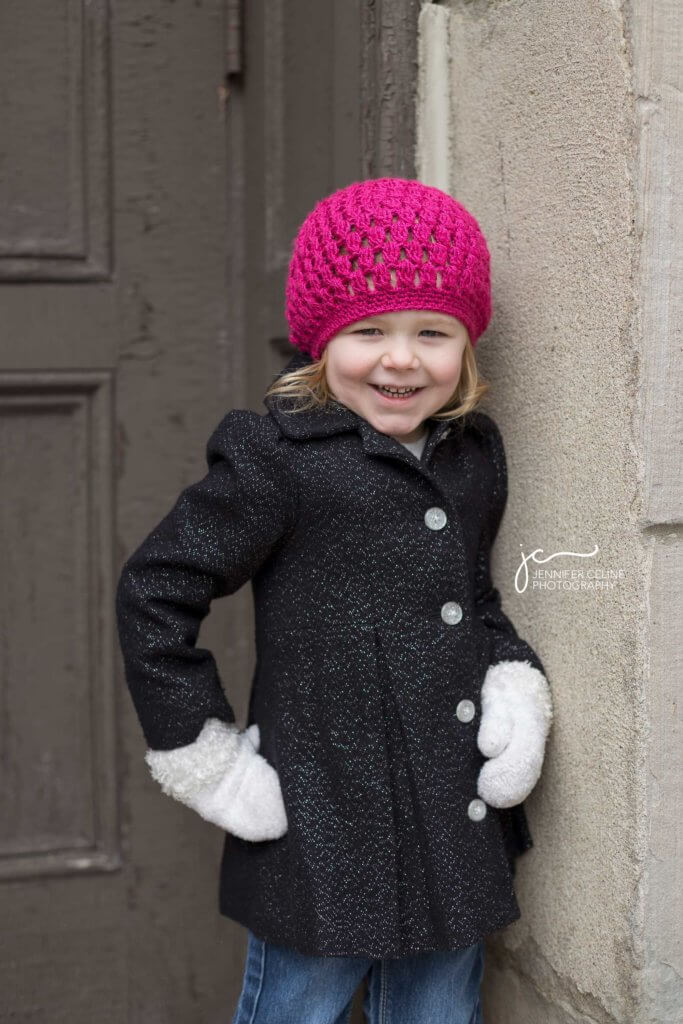 Little girl with a magenta cap on standing in a confident, sassy, hand-on-hip pose.