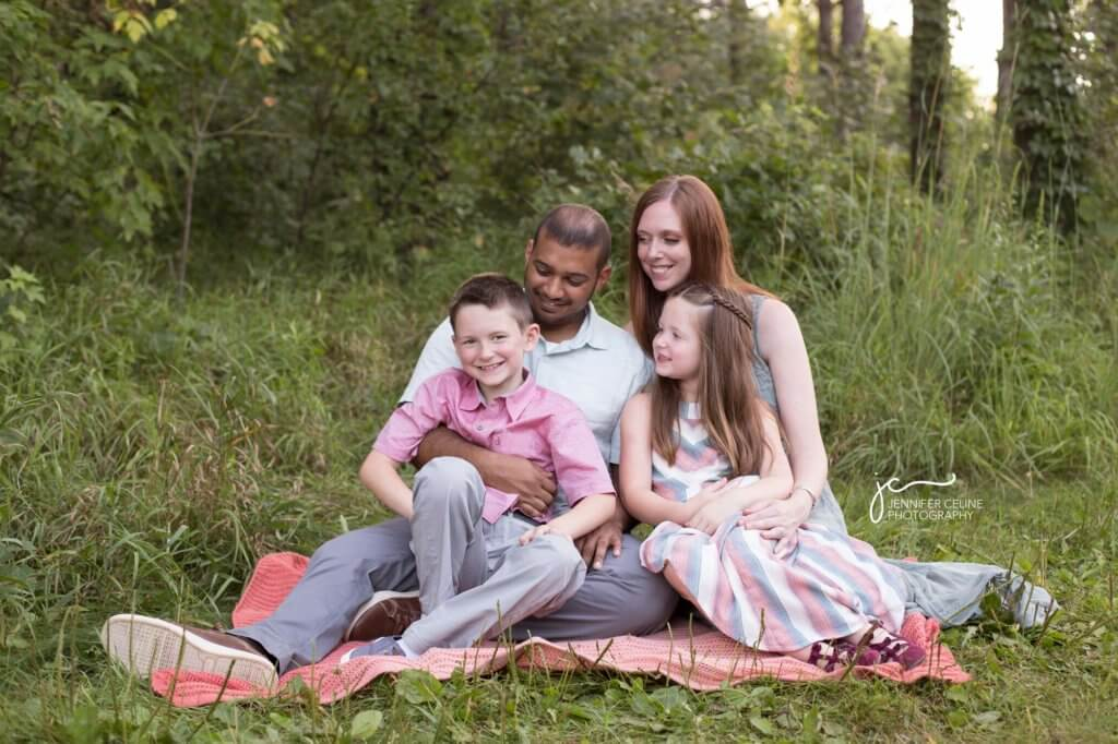Happy, smiling family of four sitting on a blanket in a grassy, wooded park area.