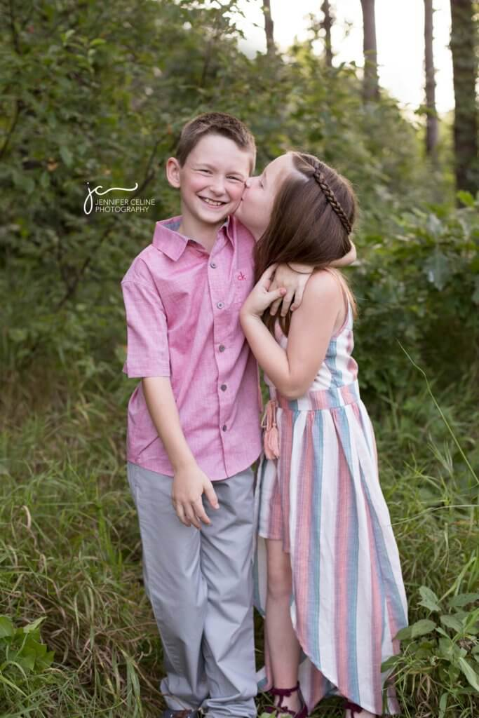 Sister giving big brother a kiss in a grassy, wooded park area