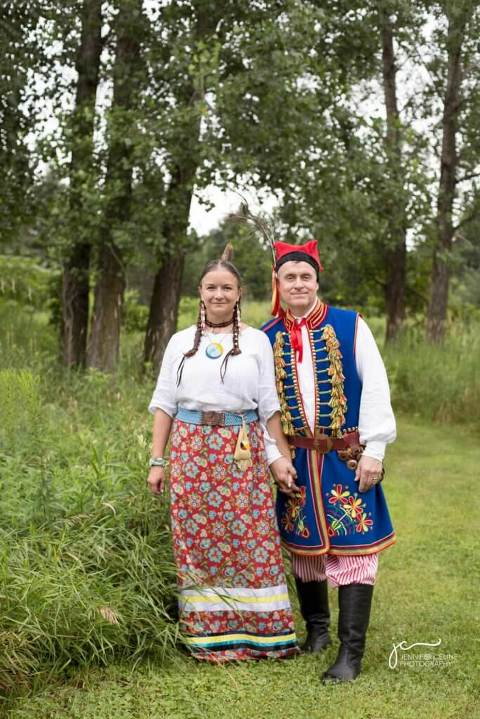 Wedding photograph of couple in grassy, wooded area in traditional Ojibwe and Polish dress.