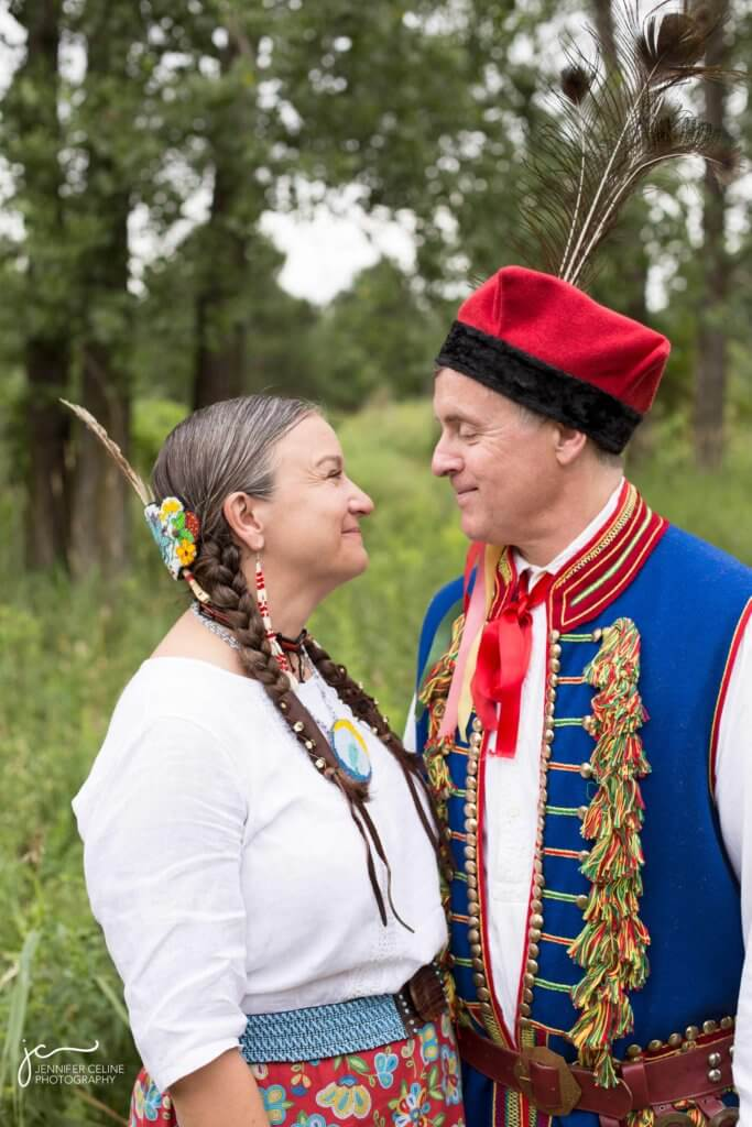 Wedding photograph of couple in grassy, wooded area in traditional Ojibwe and Polish dress looking at one another