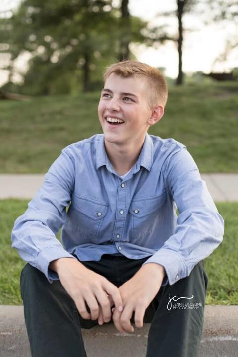 laughing high school senior male sitting on a curb in an outdoor park setting